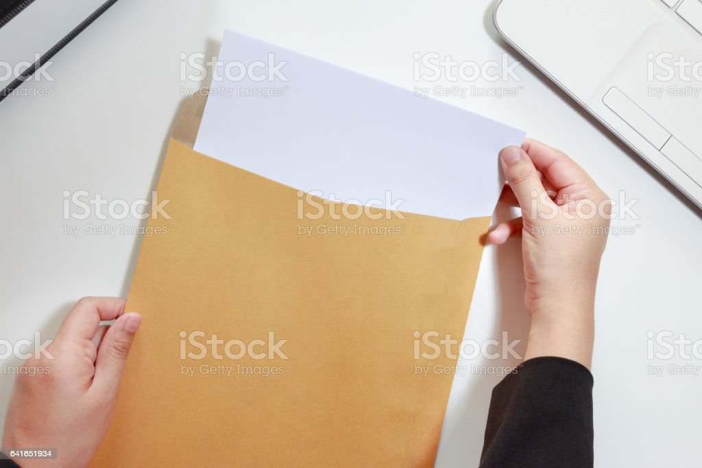 Businesswoman hands holding the blank paper in envelope stock photo