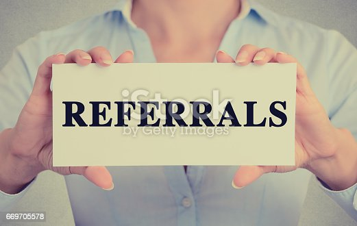 istock Businesswoman hands holding white card sign with referrals text message 669705578