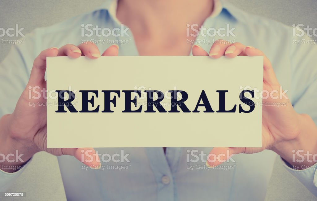 Businesswoman hands holding white card sign with referrals text message stock photo