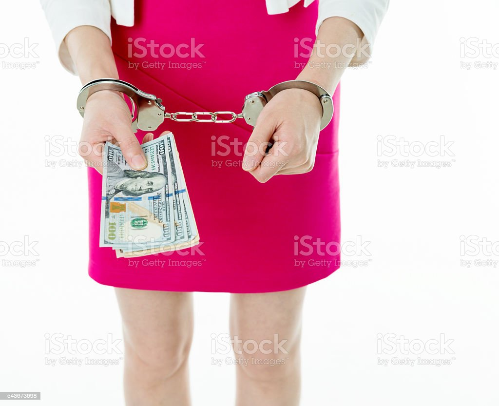 Businesswoman hands in handcuffs holding US dollars stock photo