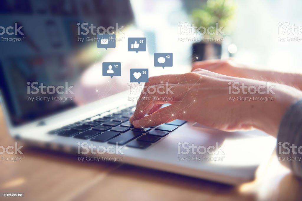 Manos de la empresaria usando laptop con icono social media y redes sociales. - foto de stock