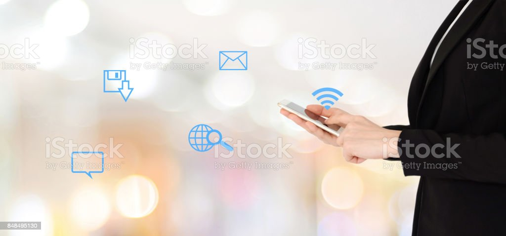 Businesswoman hands using smart phone and the internet of things icon over blur office with bokeh light background, banner, business on phone stock photo