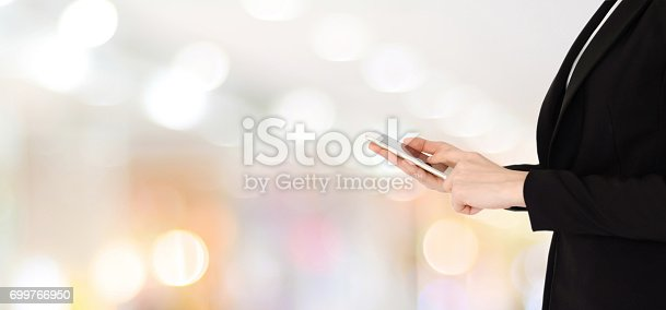istock Businesswoman hands using smart phone over blur office with bokeh light background, banner, business on phone 699766950