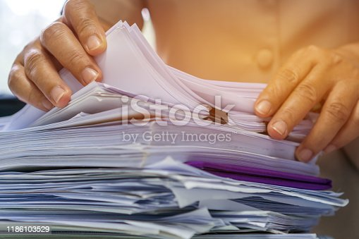 Businesswoman hands working in Stacks of paper files for searching information on work desk office, business report papers,piles of unfinished documents achieves with clips indoor,Business concept