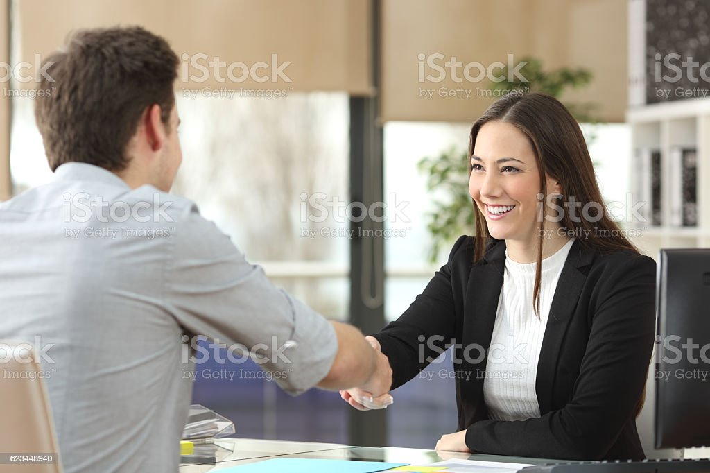 Businesswoman handshaking with client closing deal stock photo