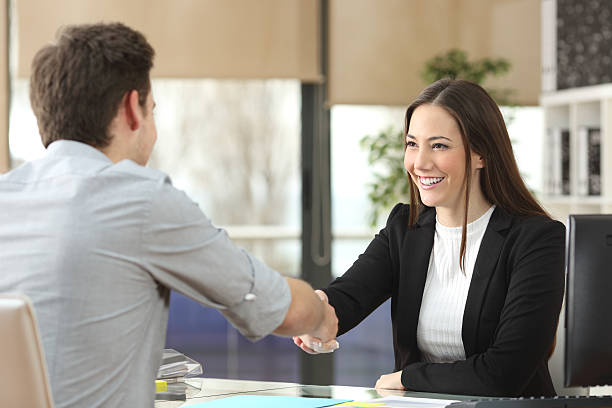 Businesswoman handshaking with client closing deal - foto de acervo