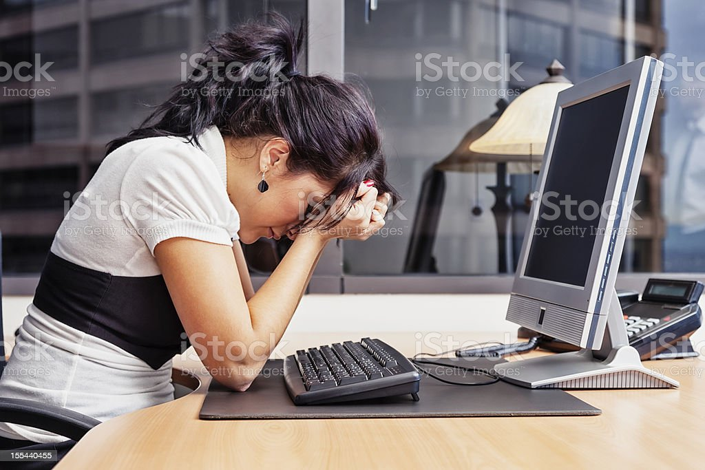 Businesswoman Having a Bad Day at The Office Photo of a businesswoman sitting at her desk with her head in her hands, as if having a very bad day. 25-29 Years Stock Photo