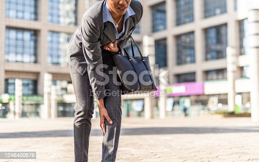 Mid adult woman having leg pain while going to work.