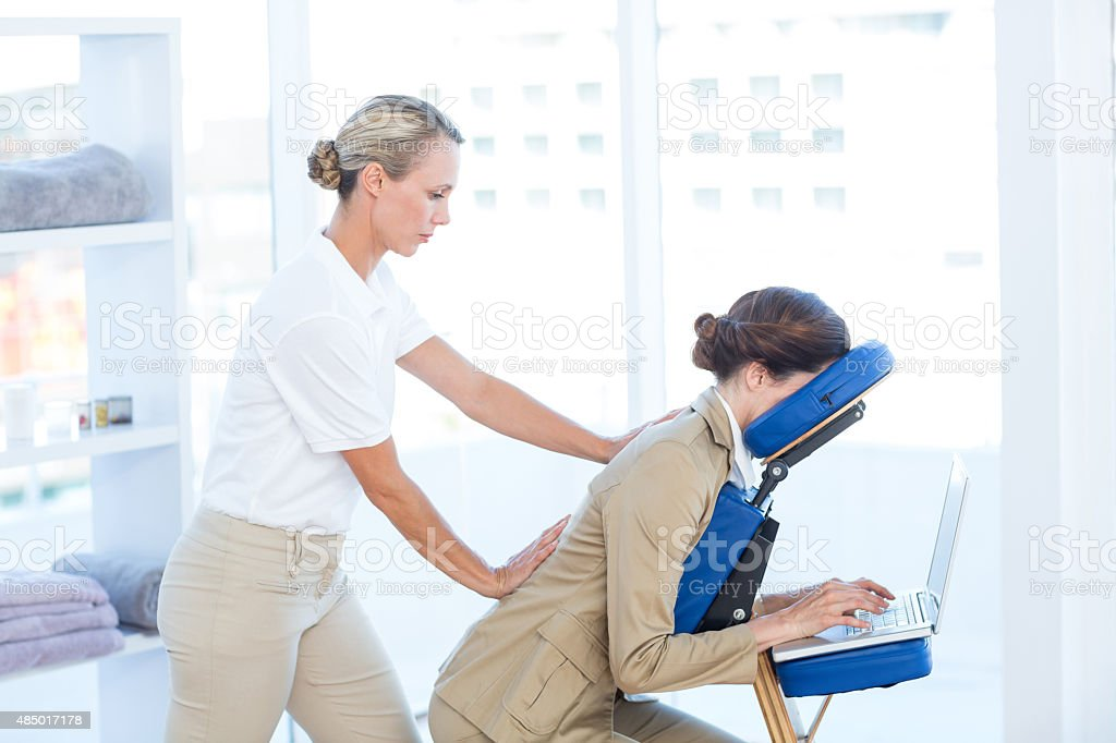Businesswoman having back massage while using her laptop stock photo