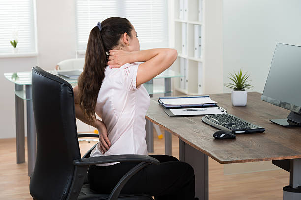 Businesswoman Having Backpain In Office Young Businesswoman Sitting On Chair Having Backpain In Office bad posture stock pictures, royalty-free photos & images