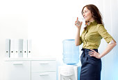 Businesswoman having a break in the office with glass of water from Water Cooler