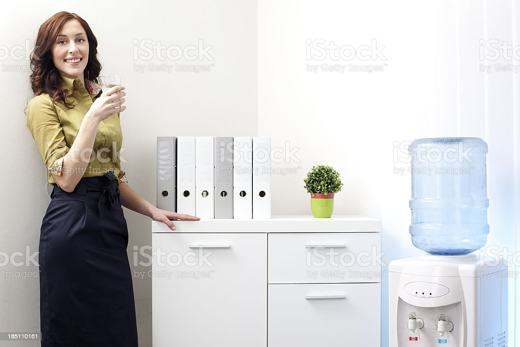 Businesswoman having drink from Water cooler. stock photo