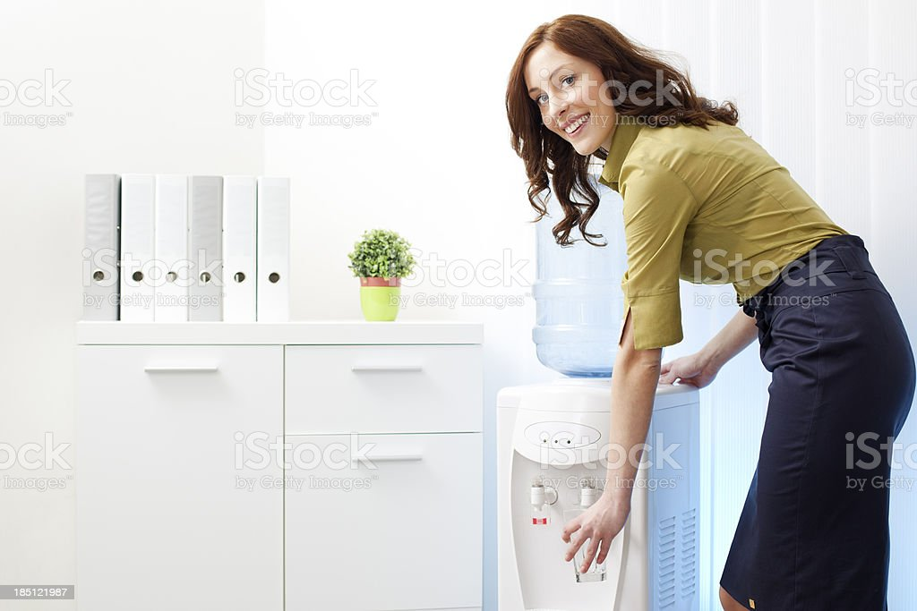 Businesswoman having drink from Water cooler stock photo