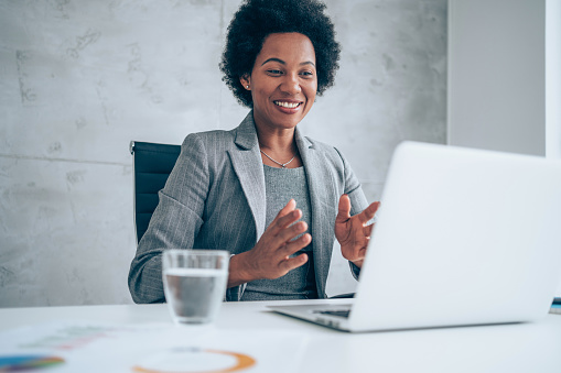 Attractive african-american businesswoman having video call with her coworkers. Businesswoman having important online conversation with customer. Shot of a young woman using a laptop for video conference. Smiling businesswoman in a video call using laptop in the office.