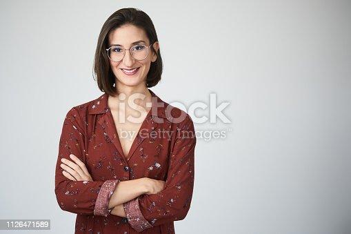 1126471588 istock photo Businesswoman headshot on grey background. 1126471589