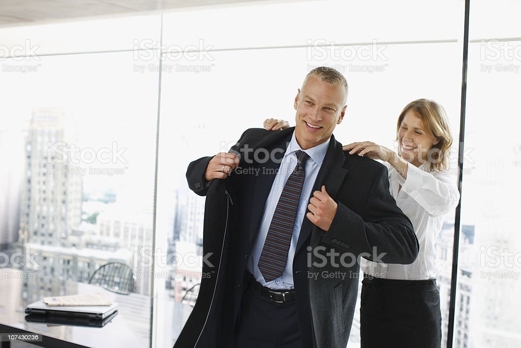 Businesswoman helping co-worker put on coat stock photo