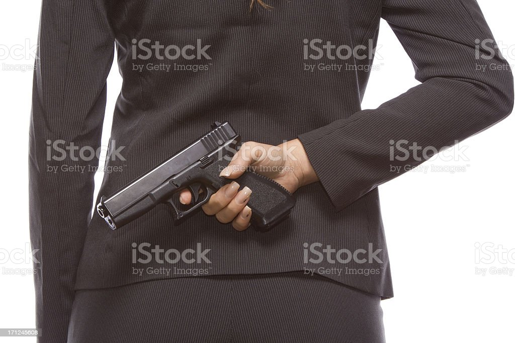Businesswoman hiding a gun behind her back royalty-free stock photo