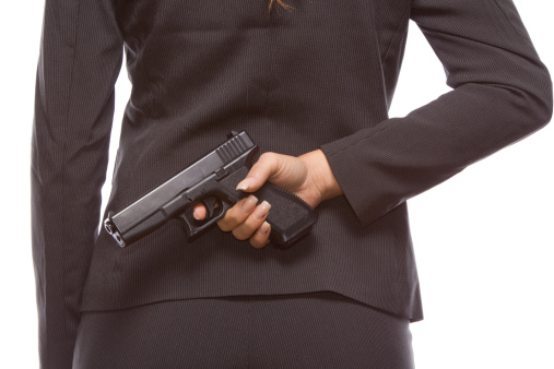 Businesswoman Hiding A Gun Behind Her Back Stock Photo - Download Image Now