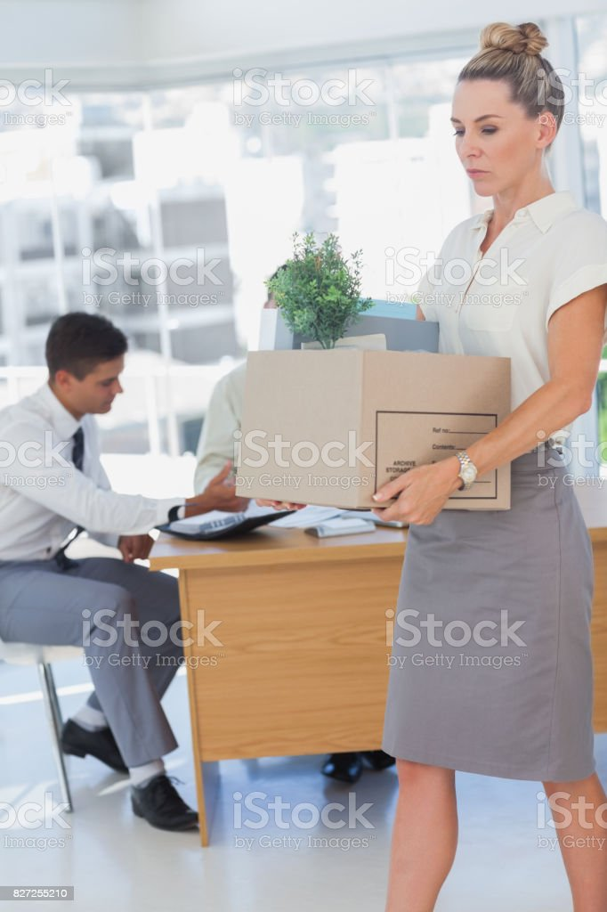 Businesswoman holding a box and his colleagues in the bottom stock photo