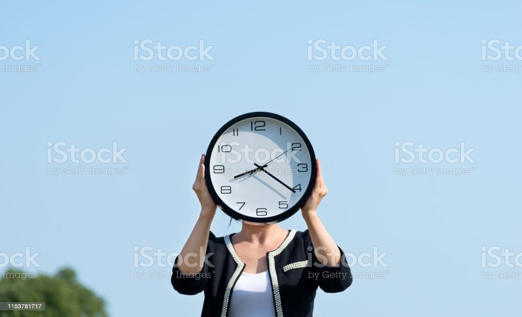 Businesswoman holding a clock in the open air.