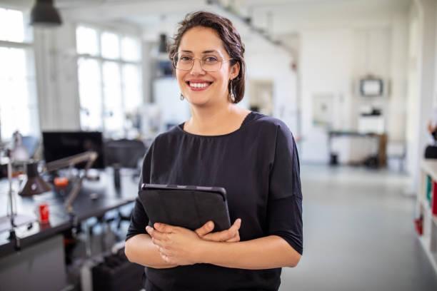 geschäftsfrau hält ein digitales tablet im büro - alvarez stock-fotos und bilder