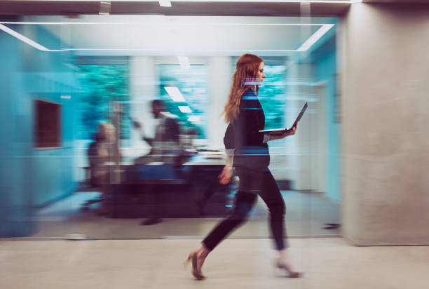 Businesswoman Holding a Laptop, Walking Down The Hallway Businesswoman Holding a Laptop, Walking Down The Hallway motion stock pictures, royalty-free photos & images