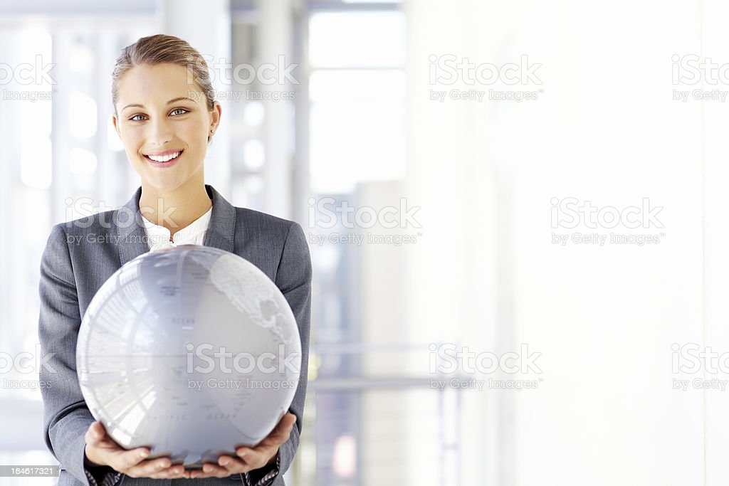 Businesswoman Holding a Large Globe stock photo