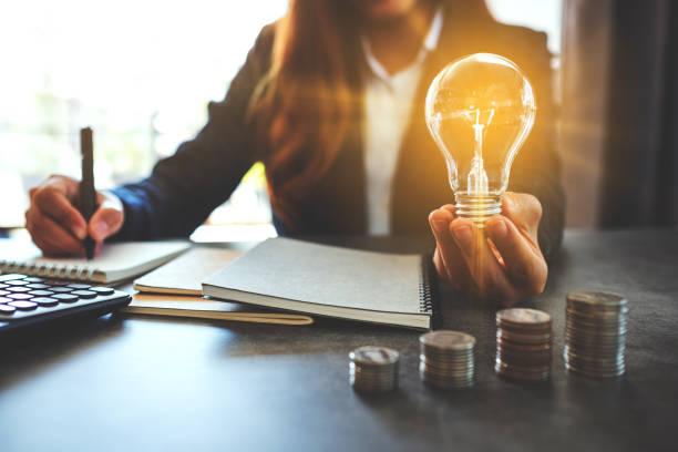 Geschäftsfrau hält eine Glühbirne, während sie Notiz auf Notebook mit Münzen Stapel – Foto
