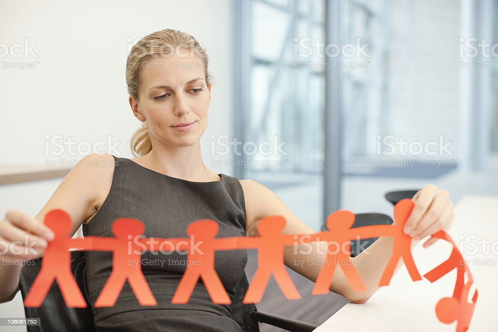 Businesswoman holding a paper cutout people royalty-free stock photo