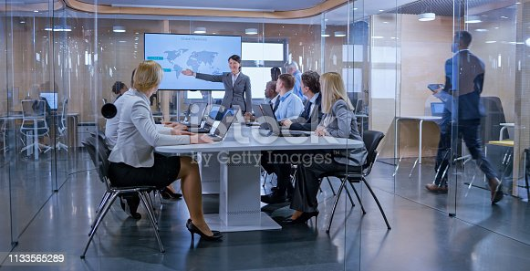 istock Businesswoman holding a presentation in glass conference room 1133565289