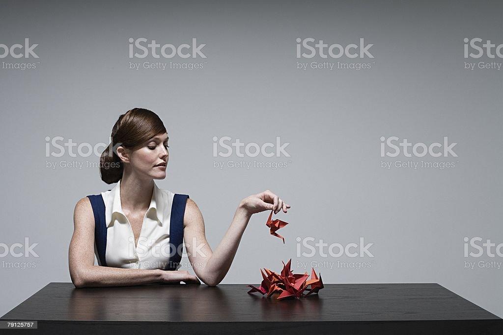 A businesswoman holding an origami bird foto de stock royalty-free
