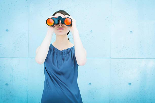 Femme d'affaires tenant une paire de jumelles - Photo