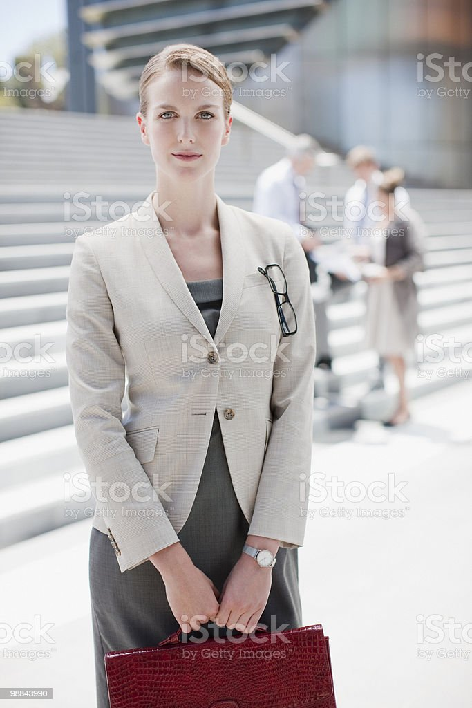 Businesswoman holding briefcase standing outdoors royalty-free stock photo