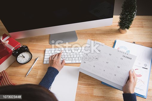 1073023470 istock photo Businesswoman holding calendar planner in christmas holiday at the office with christmas decoration on table. 1073023448