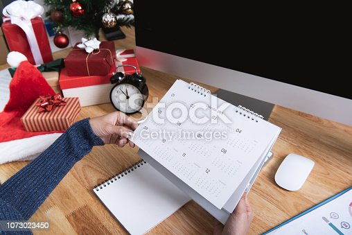 1073023470 istock photo Businesswoman holding calendar planner in christmas holiday at the office with christmas decoration on table. 1073023450