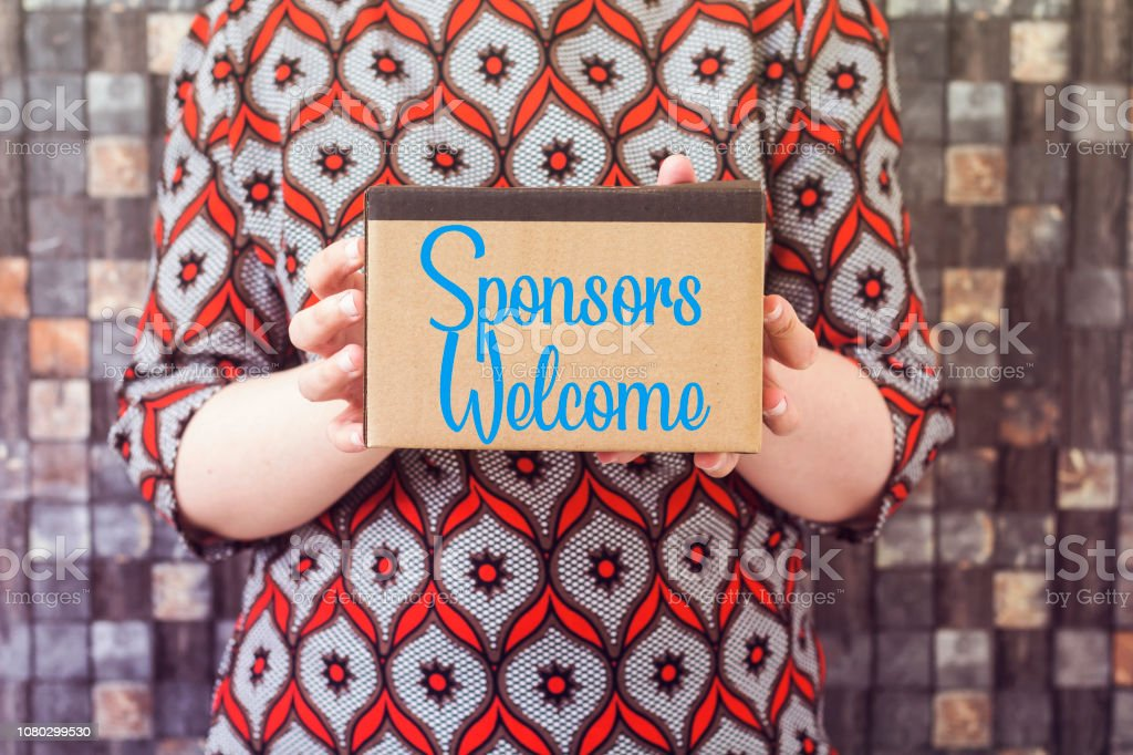 businesswoman holding cardboard with writing showing Sponsors Welcome stock photo