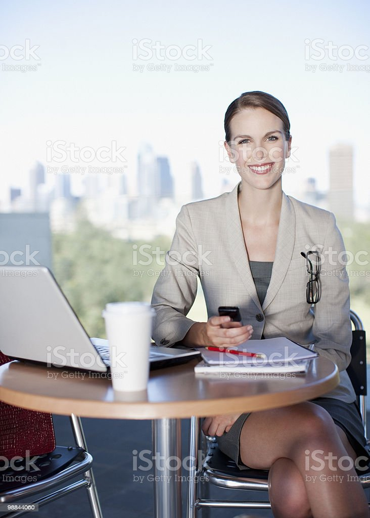 Businesswoman holding cell phone in cafe royalty-free stock photo