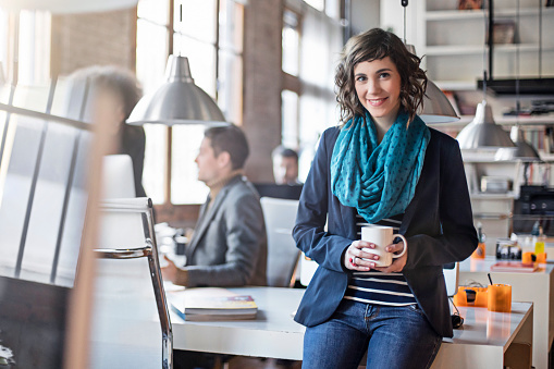 Portrait of confident mid adult businesswoman holding coffee cup. Smiling female professional is leaning on table. She is with colleagues in creative office.