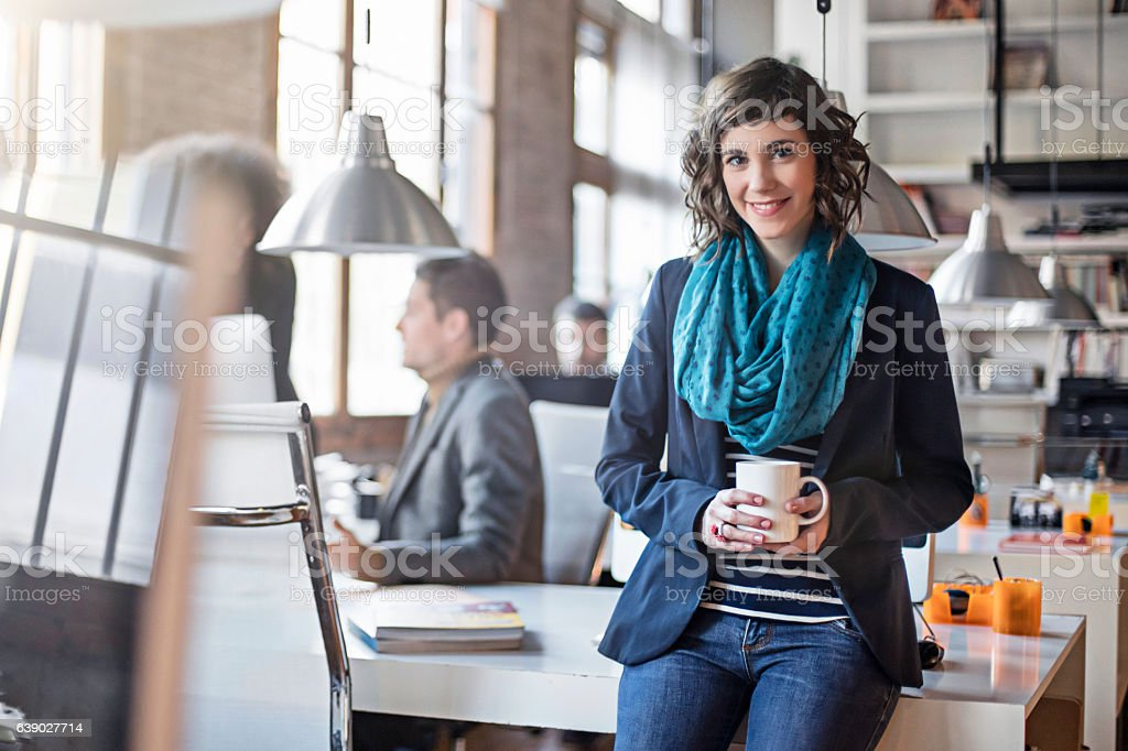 Businesswoman holding coffee cup in office stock photo