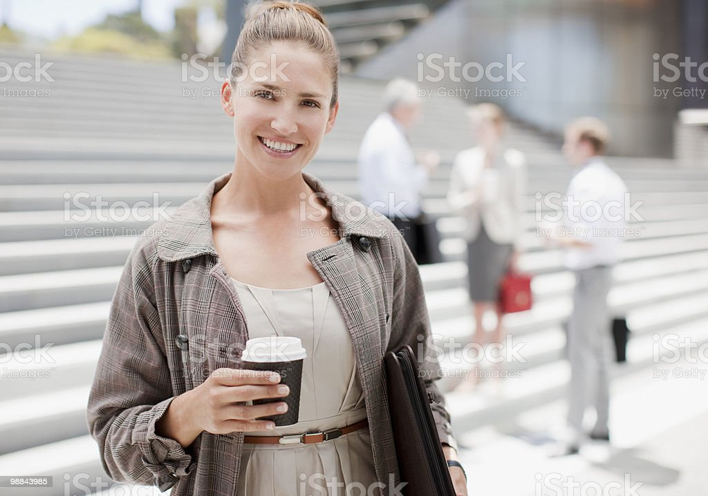 Businesswoman holding coffee outdoors royalty-free stock photo