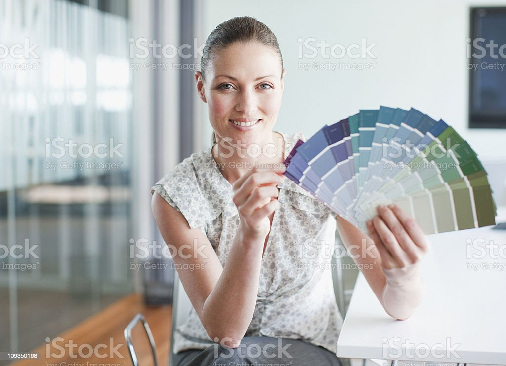 Businesswoman holding color swatches in conference room royalty-free stock photo
