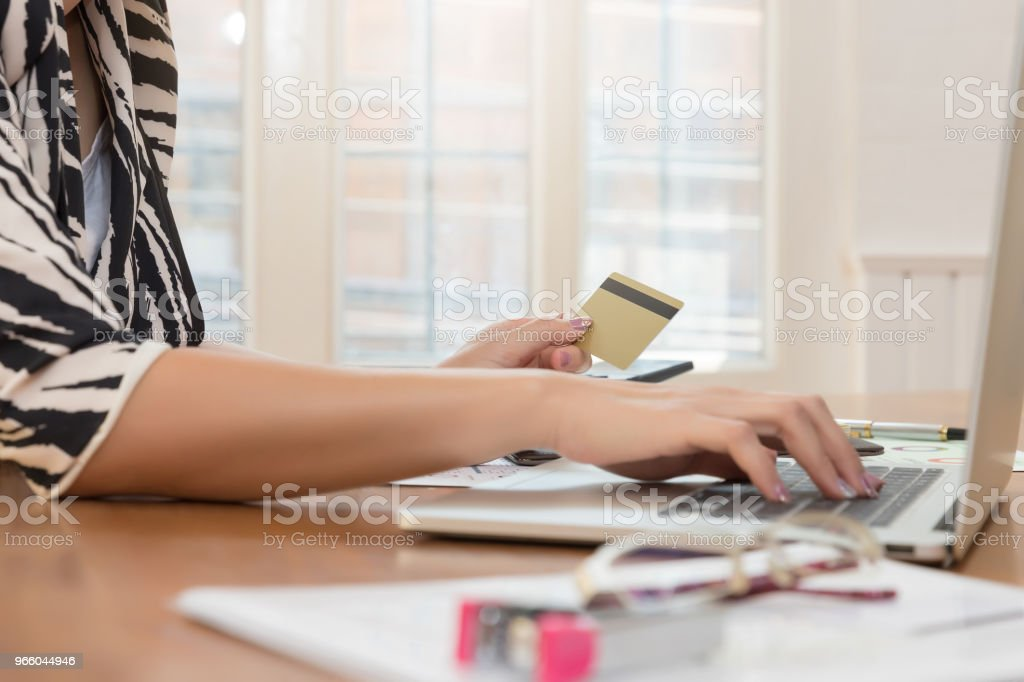 Businesswoman holding credit card and using laptop to shopping online - Royalty-free Bank - Financial Building Stock Photo