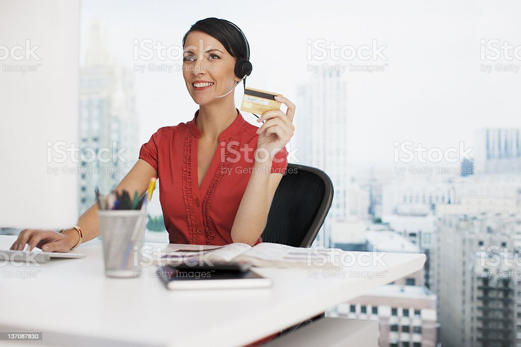 Businesswoman holding credit card at office desk royalty-free stock photo
