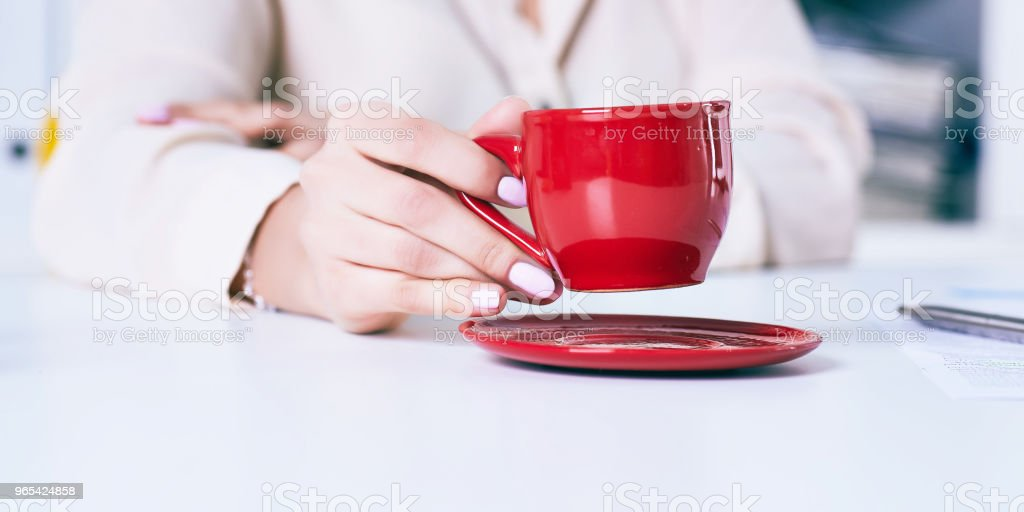 Businesswoman holding cup of coffee. Just hands over the table royalty-free stock photo