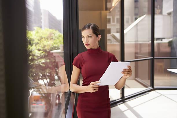 businesswoman holding document, looking out of office window - enge kleider stock-fotos und bilder