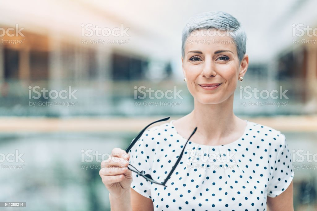 Businesswoman holding eyeglasses stock photo