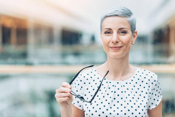 Businesswoman holding eyeglasses stock photo