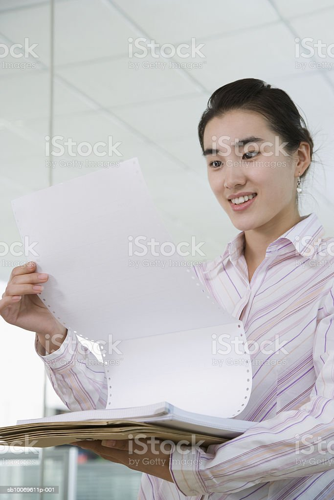 Businesswoman holding files and reading paper, smiling royalty-free stock photo