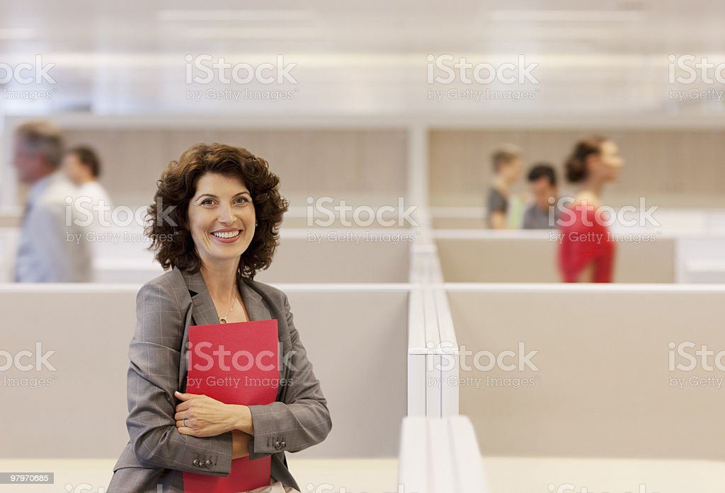 Businesswoman holding folder in office cubicle royalty-free stock photo