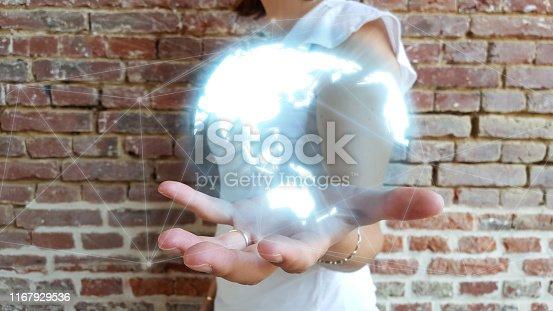istock Businesswoman holding globe network hologram 1167929536
